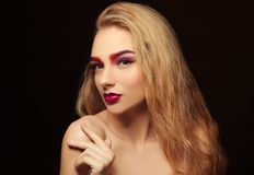 Young woman with dyed eyebrows. On black background royalty free stock photography
