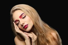 Young woman with dyed eyebrows. On black background stock photography