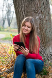 Young woman with E-book in autumn park Royalty Free Stock Images
