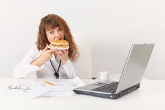 Young woman eagerly have a sandwich Stock Photography