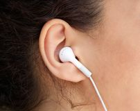 Young woman ear with earphone. Close up young woman ear with earphone royalty free stock photos