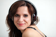 The young woman in ear-phones. The beautiful young woman in ear-phones enjoys music Royalty Free Stock Images
