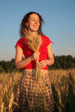 Young woman with earns on wheaten field Stock Images