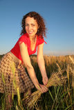 Young woman with earns on wheaten field Royalty Free Stock Images