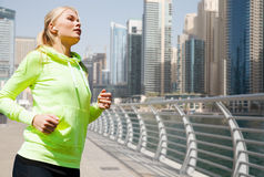 Young woman with earphones jogging outdoors Royalty Free Stock Images