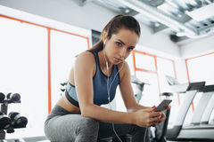 Young woman with earphones listening to music after hard workout in gym. Attractive sporty girl looking at camera with serious look and bent head. Close up Stock Photography
