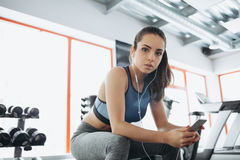 Young woman with earphones listening to music after hard workout in gym. Beautiful girl with ponytail is really tired and she is having some rest on a bench Royalty Free Stock Image