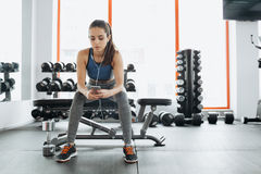 Young woman with earphones listening to music after hard workout in gym. Exhausted sporty girl sitting on the bench and having some rest Royalty Free Stock Photos