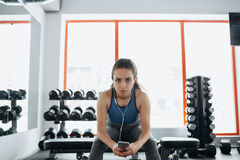 Young woman with earphones listening to music after hard workout in gym. Stock Photography