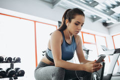 Young woman with earphones listening to music after hard workout in gym. Serious girl sitting on bench and enjoying with her the bst songs. She is exhausted Royalty Free Stock Photos