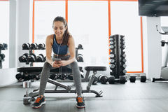 Young woman with earphones listening to music after hard workout in gym. Royalty Free Stock Images