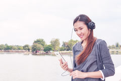 Young woman with earphones outside Royalty Free Stock Photos
