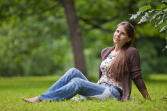 Young woman with earphones in the park. Stock Photo