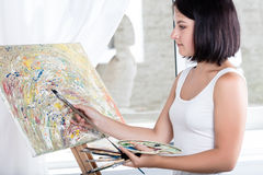 Young woman with an easel Royalty Free Stock Photos