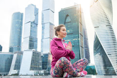 Young woman in Easy Seat pose against the skyscraper Royalty Free Stock Photos