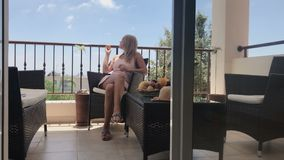 Young beautiful woman eat apricot on the balcony stock video