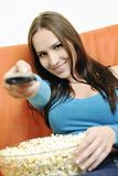 Young woman eat popcorn on orange sofa Royalty Free Stock Image