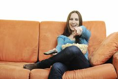 Young woman eat popcorn on orange sofa Royalty Free Stock Photo