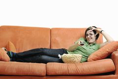 Young woman eat popcorn on orange sofa Stock Photography