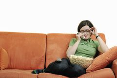 Young woman eat popcorn on orange sofa Royalty Free Stock Photography