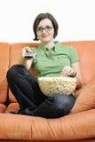 Young woman eat popcorn on orange sofa Royalty Free Stock Photo