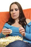 Young woman eat popcorn and watching tv Stock Images
