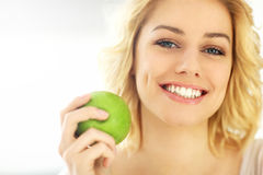 Young woman eating an apple at home Royalty Free Stock Photos