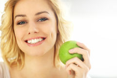 Young woman eating an apple at home Royalty Free Stock Photo