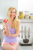 Young woman eating apple in kitchen Stock Image