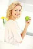 Young woman eating apple in the kitchen Stock Image