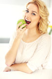 Young woman eating apple in the kitchen Royalty Free Stock Image