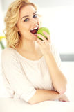 Young woman eating apple in the kitchen Stock Photo
