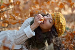 Young woman eating apple outdoor in autumn Royalty Free Stock Photos