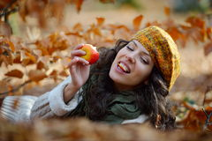 Young woman eating apple outdoor in autumn Stock Photo