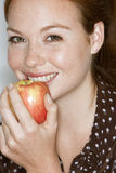 Young woman eating apple, smiling, close-up, portrait Stock Photography