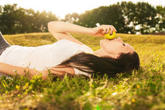 Young woman eating apple. Stunning young brunette eating apple lying on grass in sunlight Royalty Free Stock Images