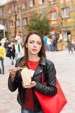 Young Woman Eating Asian Take Out at Busy Festival. Waist Up Portrait of Young Brunette Woman Eating Asian Cuisine from Take Out Box Using Chopsticks at Busy Stock Images