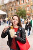 Young Woman Eating Asian Take Out at Busy Festival. Waist Up Portrait of Young Brunette Woman Eating Asian Noodle Cuisine from Take Out Box Using Chopsticks at Stock Images