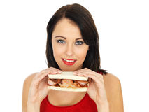 Young Woman Eating a Bacon Sandwich Royalty Free Stock Images