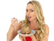 Young Woman Eating a Baked Potato with Tuna and Sweetcorn Royalty Free Stock Image