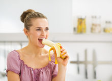 Young woman eating banana in kitchen Royalty Free Stock Photography