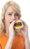 Young Woman Eating a Beef Burger Stock Images