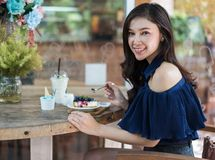 Woman eating blueberry cheese cake at cafe royalty free stock photos