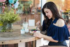 Woman eating blueberry cheese cake at cafe stock photo