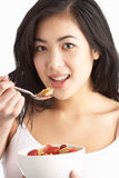 Young Woman Eating Bowl Of Cereal In Studio Stock Photography