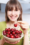 Young Woman Eating Bowl Of Cherries Stock Image