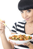 Young Woman Eating a Bowl of Colourful Vegetarian Tomato Pasta Stock Photo