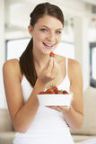 Young Woman Eating A Bowl Of Fresh Strawberries Stock Images