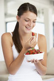 Young Woman Eating A Bowl Of Fresh Strawberries Stock Photos