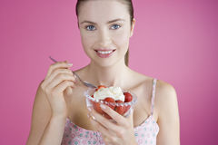 A Young Woman Eating A Bowl of Strawberries And Cream Royalty Free Stock Photography